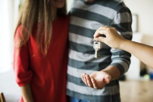 Young couple holding the keys to their new home.
